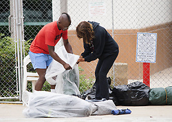 August 7, 2017 - Tustin, CA, USA - Homeless advocate Tyron Jackson, left, helps a woman organize her belongings into plastic bags at the civic center in Tustin, CA on Monday, August 7, 2017. The city posted signs at the civic center telling people living in the homeless encampment that they must move out by 8 a.m. to make way for a temporary library. (Credit Image: © Ken Steinhardt/The Orange County Register via ZUMA Wire)