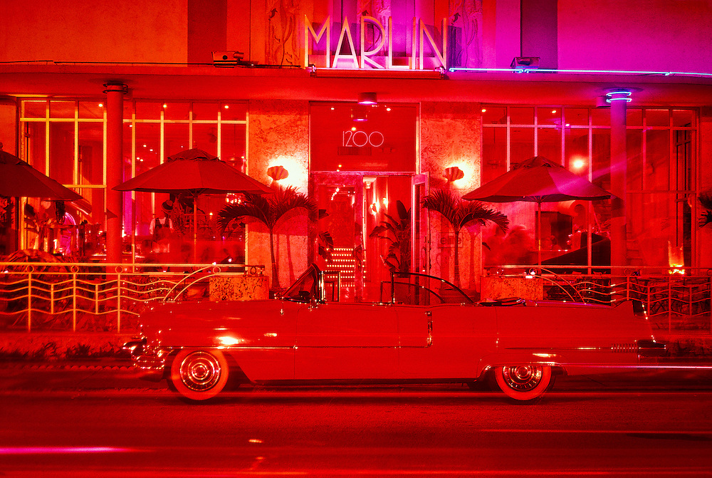 The streamlined, Marlin Hotel on Miami Beach's neon-lit Collins Avenue with a vintage, pink, 1956 Cadillac convertible parked in front. <br /> <br /> The Marlin was designed in 1939 by  L. Murray Dixon, one of the master architects  of South Beach's signature Tropical Deco style.<br /> <br /> Island Record and movie mogul Chris Blackwell restored  the building beautifully in the early 1990s and added a small recording studio inside the hotel.