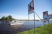 Een plezierboot vaart het Margrietkanaal bij Grou op. Diverse borden aan het begin van het kanaal attenderen schippers op het drukke scheepvaartverkeer. Op het kanaal mag niet gezeild worden en de middenweg moet vrij gehouden worden voor de vrachtschepen. De kruising tussen plezier- en beroepsvaart levert vaak tot problemen. Zeker als bij het mooie weer veel beginnende schippers het water opgaan.<br /> <br /> A boat is entering the Margrietkanaal near Grou. Signs are warning sailors for the commercial shipping. The channel may not be sailed and the middle way must be kept free for the freighters. The intersection between pleasure and commercial vessels often leads to problems. Especially with  many novice sailors.