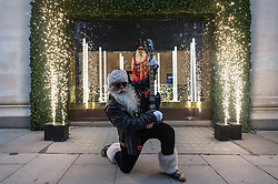 © Licensed to London News Pictures. 18/10/2018. London, UK. A man dressed as Santa Claus launches the Selfridges department store Christmas festive window display with a 'Selfridges Rocks Santa' theme. It is the first department store in the world to unveil Christmas windows. Photo credit: Ray Tang/LNP