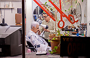 Retro America - Man getting haircut in old barber shop. Weehawken, NJ