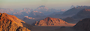 Distant mountains and sandstone cliffs at sunrise in Wadi Rum, Jordan.