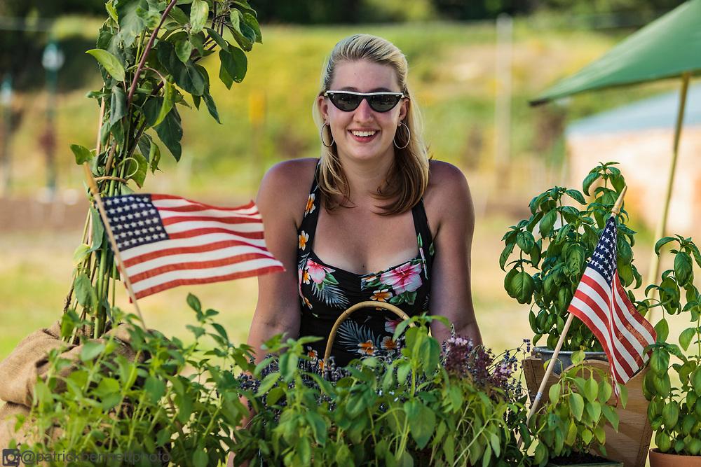 Dottie Jo Kite waves a flag in front of her plant sale along the sidewalk in Palouse, WA.