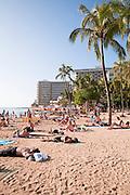 Crowds of people sunbathe on Waikiki Beach.