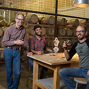 Tucson, AZ -- 09/28/2017<br /> <br /> (L- R) Hamilton Distillers founder Stephen Paul, assistant distiller Ramón Olivas and his dog Scarlet and head distiller and maltser Nathan Thompson Avelino photographed in the tasting room at the Tucson distillery. <br /> <br /> Hamilton Distillers, makers of Whiskey Del Bac, is the first craft distillery in Southern Arizona since prohibition. The company produces three distinct single malt whiskeys, including Whiskey Del Bac Dorado which is malted over mesquite.<br /> <br /> The distillery offers tours and tastings on Saturdays at 3 p.m <br /> <br /> Photography by Jill Richards