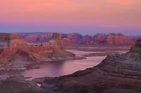 Pastel sandstone formations glow at dusk above Lake Powell, Utah.
