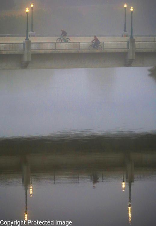 Two cyclists pedal through the morning fog over the Laurel Street Bridge in downtown Santa Cruz. <br /> Photo by Shmuel Thaler <br /> shmuel_thaler@yahoo.com www.shmuelthaler.com