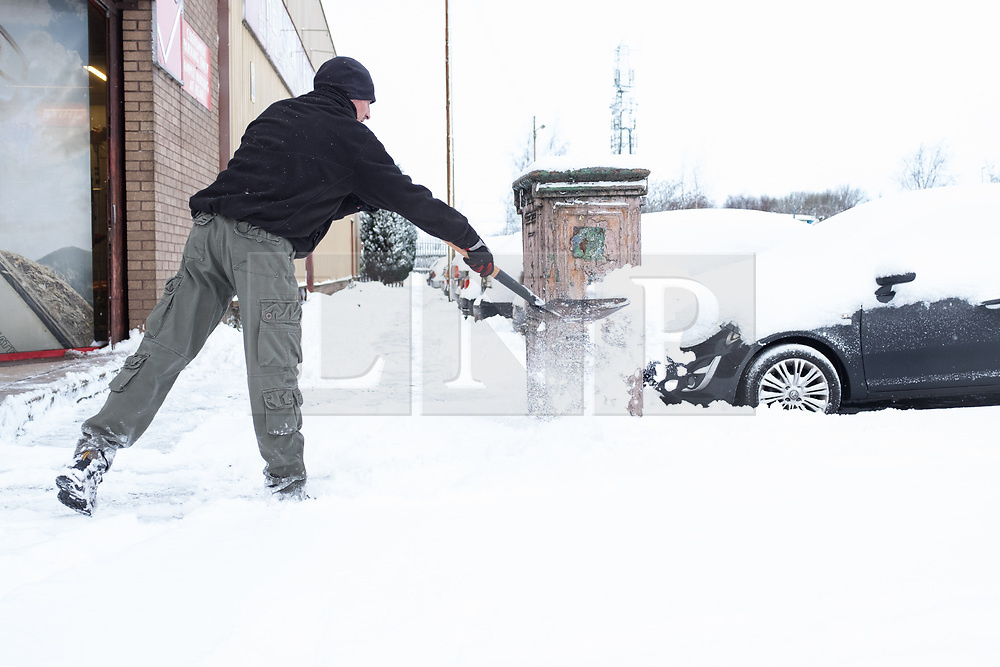 """© Licensed to London News Pictures. 28/02/2018. <br /> <br /> A man clears the pavement outside a hardware store as Glasgow, Scotland is hit with snow storm """"Beast from the East"""" on 28th February 2018.<br /> <br /> Photo credit should read Max Bryan/LNP"""