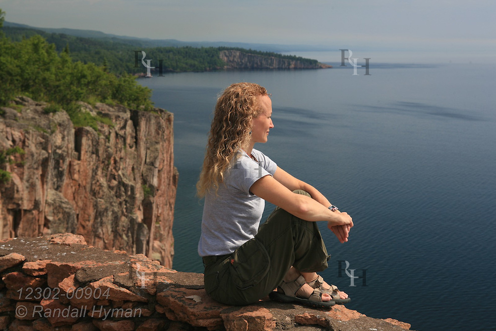 Woman sits atop cliff at Palisade Head in Tettegouche State Park overlooking clear blue waters of Lake Superior, Minnesota.