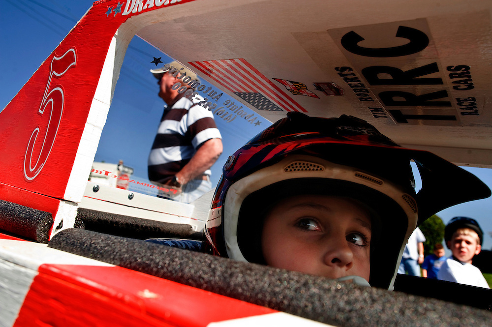 (staff photo by Matt Roth)..Dragon Hornatko, 8, from Arbutus, sits in his souped-up soapbox derby -- complete with an in-dash stereo before the start of the first race of the day. The annual fourth of July Arbutus Soapbox Derby almost didn't happen, according to Allan Arca, 51, son of the race's long-time coordinator Paul Arca who has been in and out of the hospital with failing kidneys recently. The senior Arca's attention to his health has taken his time away from prepping for the derby. The Arca family is asking that someone step-up to take over the derby for 2010. Only five cars showed up to race at the intersection of Elm and Oakland. (here's the Arca's number I was given: 410-242-0806)