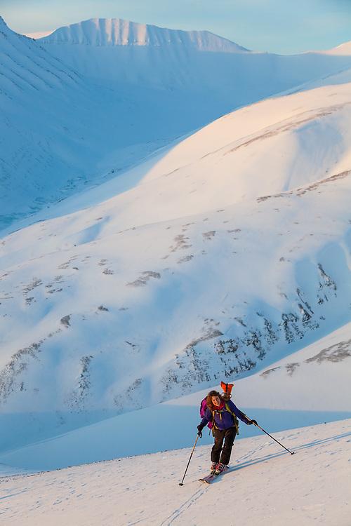 Mylène Jacquemart skins up a hillside at sunset in Koslådalen, Svalbard.