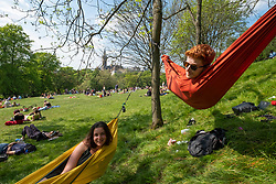Glasgow, Scotland, UK. 15 May 2019. Warm sunny weather in the city brought hundreds of young sun-seekers to Kelvingrove Park in the city's West End. Pictured Miriam and Dom enjoy they hammocks strung from trees in the park.