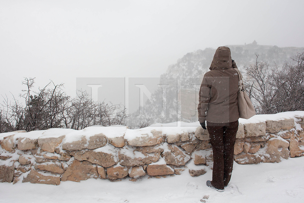 © Licensed to London News Pictures. 07/12/2013. Grand Canyon Village, USA. As blizzards affect parts of the United States a tourist braves heavy snow on the rim of the Grand Canyon during a 'white out' in Arizona today (07/12/2013). The canyon, one of the world's 'Seven Wonders', experienced temperatures of around -18 degrees celsius before the heavy snow caused a 'white out' causing visitors to be refused entry to the park at around 13:00 MST (Mountain Standard Time). Photo credit: Matt Cetti-Roberts/LNP