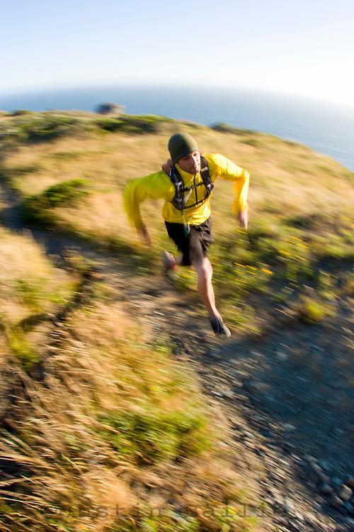 Young man running near the California Coastal Trail; Golden Gate National Recreation Area. San Francisco,  CA.