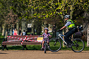 A police offoicer and Community Support Officer patrol the common to gently make sure the public comply with guidance - Good Friday - Clapham Common is pretty quiet after Lambeth Council  taped up all the benches, put signs out and painted reminders of the 2m distancing on the paths. The 'lockdown' continues for the Coronav. The 'lockdown' continues for the Coronavirus (Covid 19) outbreak in London.