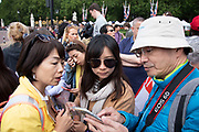 Asian tourists look at a map on a  smartphone while navigating their way around London, England, United Kingdom.