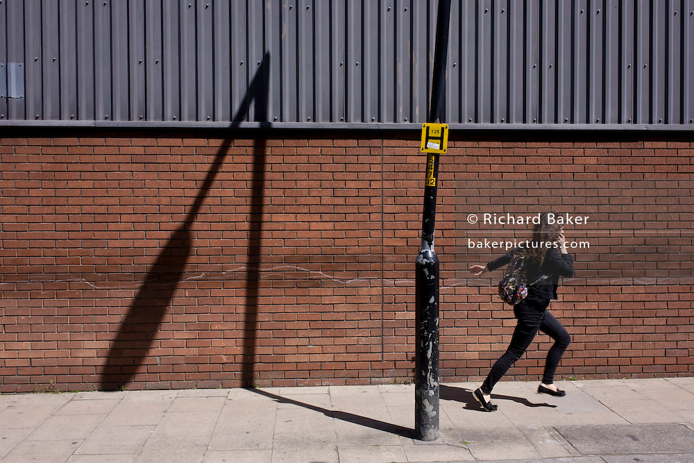 Girl runs past a leaning post and its own shadow on a brick wall in south London. In an urban landscape of angles and diagonals, we see the bent nature of vertical upright lines against the straight parallels of corugated wall sheeting, showing the random, off-true setting of the lamppost, in a side street in Southwark, south London.