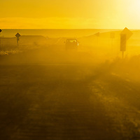 010813  Adron Gardner/Independent<br /> <br /> Sunrise illuminates dust kicked up by a truck at the  unpaved junction of Navajo Route 71 with the paved Navajo Route 2 near Winslow Wednesday.