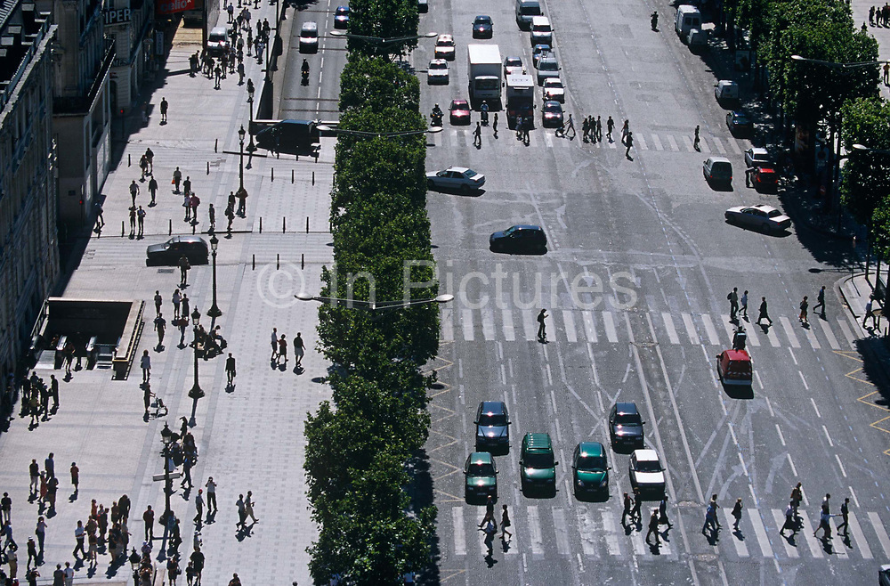 Viewed from the top of the Arc de triumph in the centre of Paris, the French capital, we see tiny human figures going about their daily business, a hurried frenzy of activity at street level far below. This street is the Avenue des Champs Elysees, one of the most famous of European boulevards and the multi-lane road that stretches away into the distance – from l'Etoile to Place de la Concorde – is dissected with zebra crossings over which more pedestrians negotiate the Parisian traffic that has stopped on a red light. Otherwise small figures walk along the pavement (sidewalk) and some disappear into an underground Metro entrance.