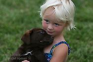 Four-year-old girl cuddles with puppy on her farm in Lee County, southeast Iowa.