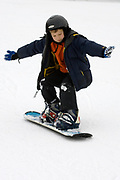 9 year old boy riding his snowboard.