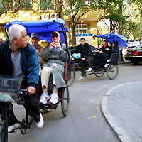 Asia, China, Beijing.  Rickshaw pedicabs turn the corner taking tourists into the hutong neighborhoods of Beijing.