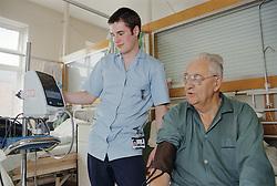 Student nurse taking patient's blood pressure on medical ward,
