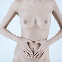 studio shot picture of a young beautiful breast naked caucasian woman joining hands in a heart shape on her belly