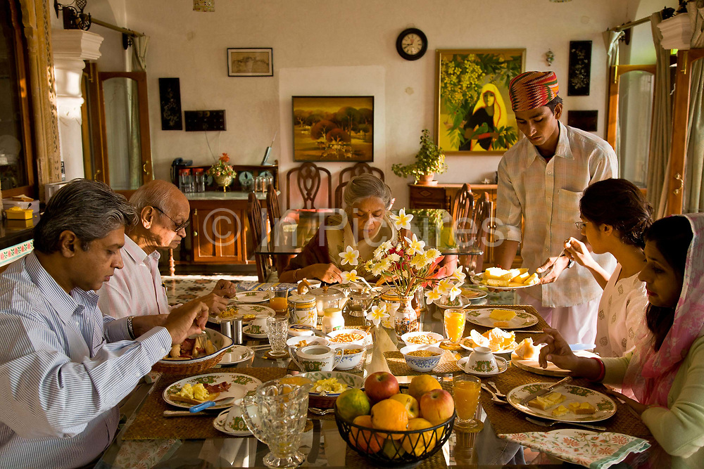 """Nobleman Nahar Singhji, also known as Rao Saheb (center left), with his wife Rani Saheb (center), son, daughter-in-law and grandaughter, enjoy a relaxed breakfast in their lake side home on the grounds of the Deogarh Mahal Palace, now a heritage hotel.  This architectural jewel was, prior to it becoming so in 1996, a fortress - palace, dating back 340 years. It belonged to the Mewar aristocracy, their magnificent fort a fitting stronghold for one of its sixteen """"umraos"""" - the most senior feudal barons attending on the Maharana of Udaipur, Rajasthan,"""