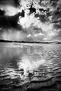Sunshine, squalls, showers, dramatic skies reflected in the rippled wet sand of Traeth Lligwy Beach, East Anglesey.
