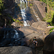 Man sitting on the rocks in Seven Wells waterfalls, Langkawi, Malaysia
