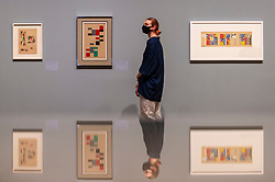 © Licensed to London News Pictures. 13/07/2021. LONDON, UK. A staff member poses with a variety of designed for an interior design project.  Preview of the first UK retrospective exhibition at Tate Modern of works by Sophie Taeuber-Arp (1889-1943), one of the foremost abstract artists and designers of the 1920s and 30s. Works from Taeuber-Arp's accomplished career as a painter, architect, teacher, writer, and designer of textiles, marionettes and interiors is on 15 July – 17 October 2021.  Photo credit: Stephen Chung/LNP