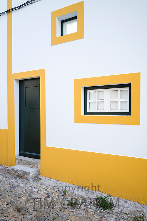 Typical colours of Evora - white and yellow geometric box house with dark green front door in cobble street in Evora, Portugal