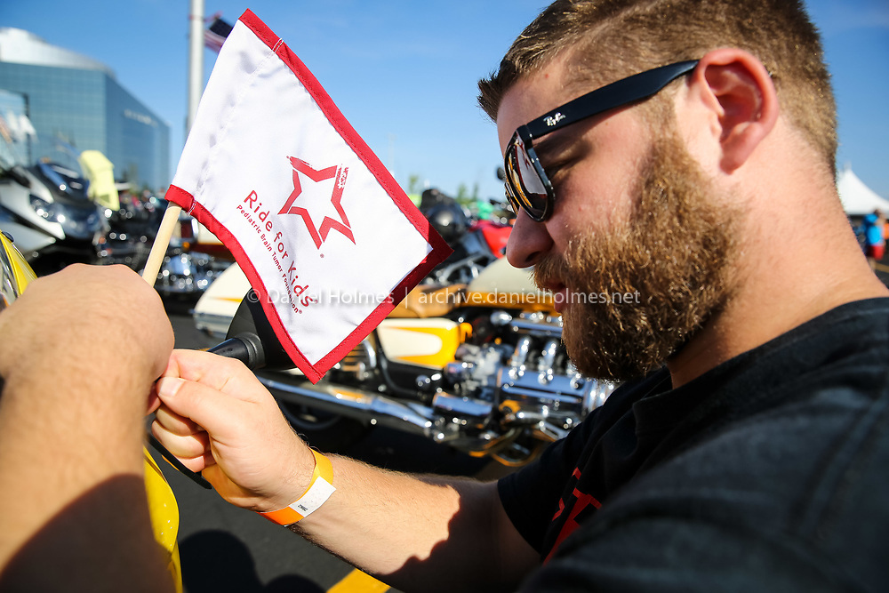 """(8/28/16, FRAMINGHAM, MA) Cody Taylor, of Waltham, attaches a """"Ride for Kids"""" flag to his motorcycle during the Pediatric Brain Tumor Foundation Ride for Kids at Bose in Framingham on Sunday. Daily News and Wicked Local Photo/Dan Holmes"""