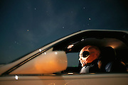 """Roswell """"alien"""". An alien figure sits in a car at night on the outskirts of the town of Roswell, New Mexico, USA. It was near Roswell on the evening of 2 July 1947 that many UFO sightings were reported during a thunderstorm. Next morning a rancher, Mac Brazel, discovered strange wreckage in a field. When the impact site was located, a UFO craft and alien bodies were allegedly found. On 8 July 1947, the Roswell Daily Record announced the capture of a flying saucer. The official explanation was that it was a crashed weather balloon. Many Roswell inhabitants, however, believe this a cover up, and Roswell has become a symbol for UFO enthusiasts. Photo illustration. (1997) ."""