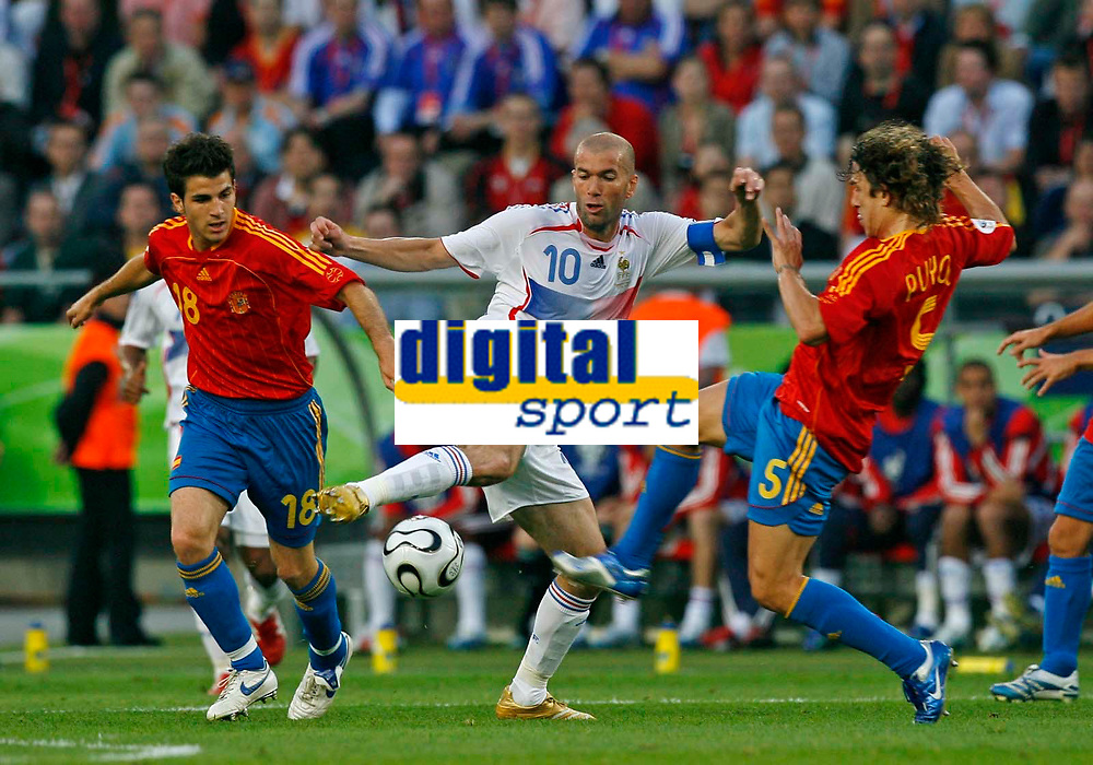 Photo: Glyn Thomas.<br />Spain v France. Round 2, FIFA World Cup 2006. 27/06/2006.<br /> France's Zinezine Zidane (C) plays the ball under pressure from Spain's Cesc Fabregas (L) and Carlos Puyol.