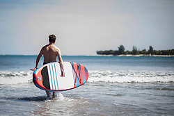 Rear view of man carrying surfboard while walking into sea, Mauritius
