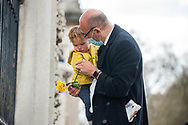 A member of the public lays flowers with his child In memory of Prince Philip The Royal Highness the Duke of Edinburgh, London on 9 April 2021.