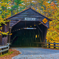 The historic Durgin Covered Bridge framed by New England fall foliage. Durgin Covered Bridge spans the Cold River and is located in Sandwich, New Hampshire.<br />
