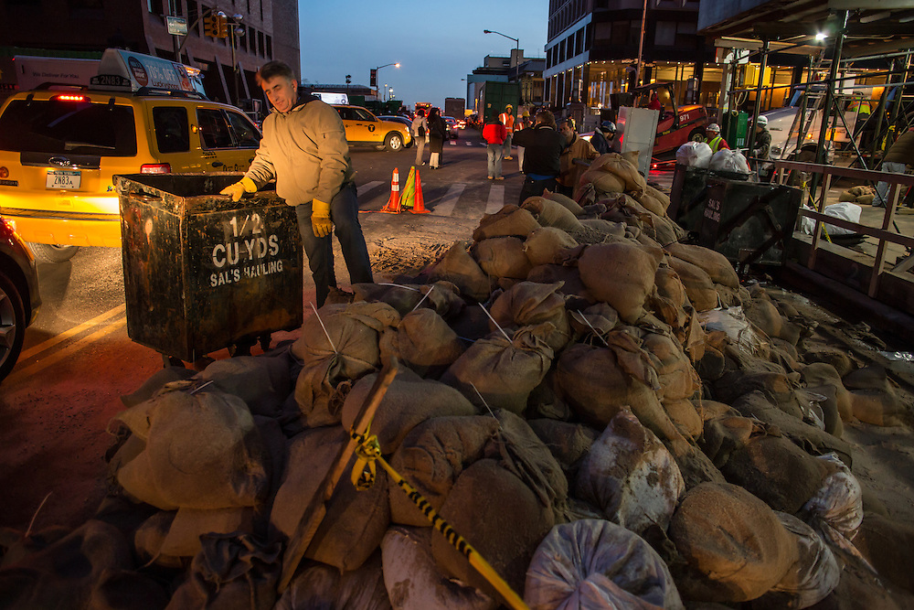 Workers remove sandbags on Water Street. The sandbags are being loaded into small carts by hand, then emptied into roll-away containers.