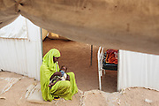 A woman gives her child some water to drink as she sits outside a tent at a UNICEF-sponsored therapeutic feeding center at the Mongo hospital in the town of Mongo, Guera province, Chad on Tuesday October 16, 2012.