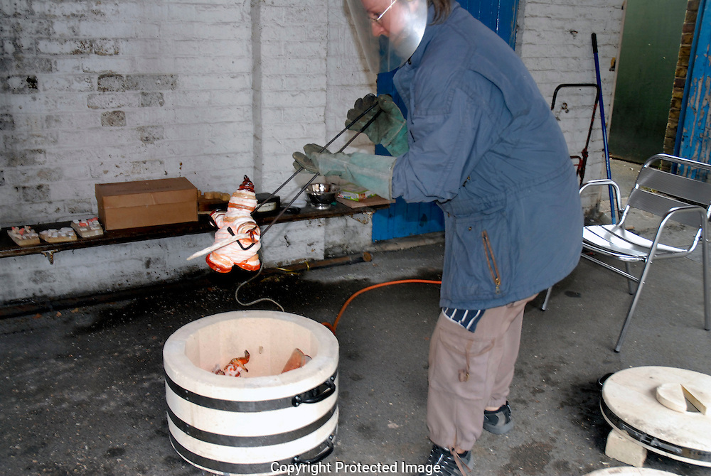 Making pottery using  Raku a traditional method of firing pottery