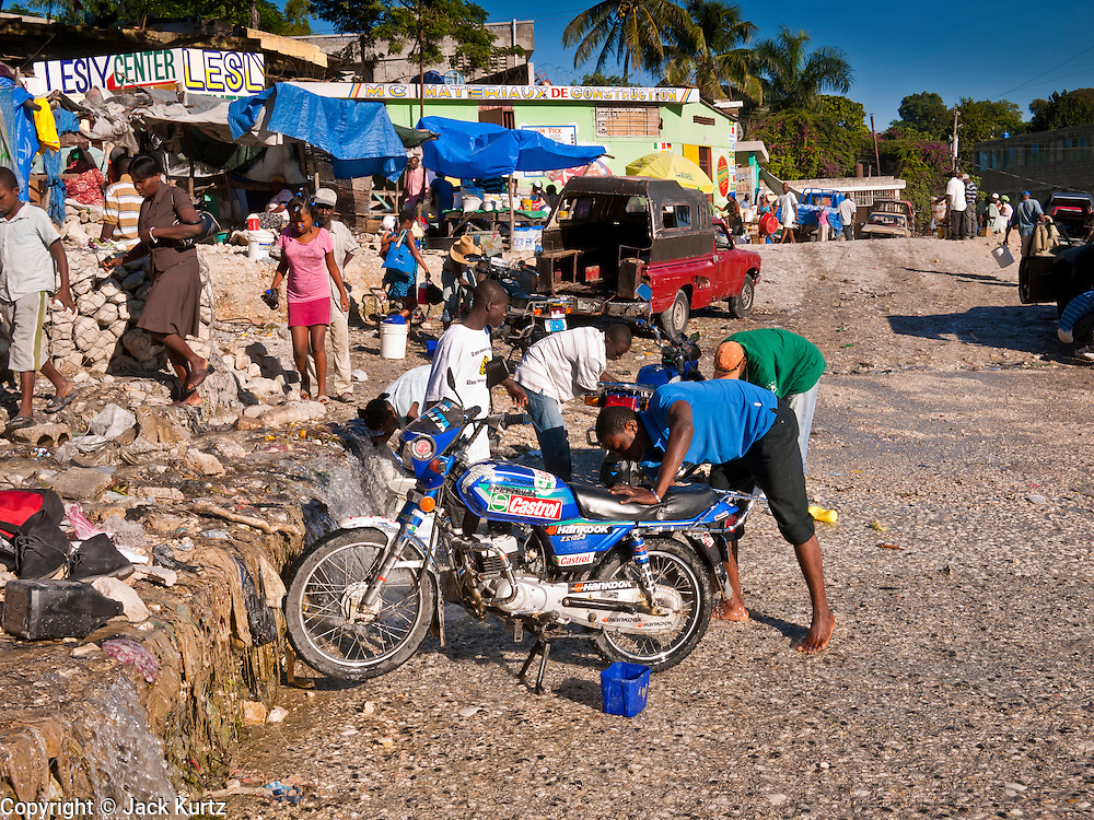 18 NOVEMBER 2010 - PORT-AU-PRINCE, HAITI: Men wash their motorcycles at a stream that runs through a suburb of Port-au-Prince, Haiti, Thursday morning.  An outbreak of cholera in northern Haiti about a month ago has spread across the nation. Tens of thousands of people have been hospitalized and treated for cholera and more than 1,100 have died. Cholera is a water borne illness that causes severe diarrhea and death by dehydration in a matter of hours.    PHOTO BY JACK KURTZ  choleraepidemic