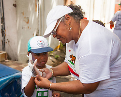 Lisa Hunt helps grandson David Dennis don gloves for the cleanup.  Residents and volunteers gather for the Garden Street neighborhood cleanup and block Party hosted by E's Garden and Things, Long Path/Garden Street Community Association, and the Economic Development Authority's Enterprise and Commerical Zone Commission.  St. Thomas, USVI.  5 September 2015.  © Aisha-Zakiya Boyd