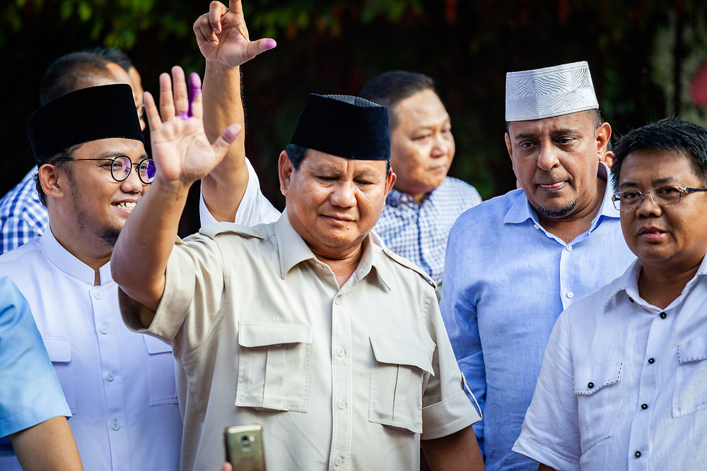 After his address claiming that he is leading at the polls against his opponent Joko Widodo, Prabowo Subianto, presidential candidate of Indonesia, gestures to his supporters that has gathered in front of Kerta Negara, West Jakarta, Indonesia, on Wednesday April 17, 2019. Photographer: Andri Tambunan/Bloomberg<br /> <br /> <br /> Security holds back the crowd that has gathered in front of Kerta Negara, West Jakarta, Indonesia, on Wednesday April 17, 2019. Prabowo Subianto, presidential candidate of Indonesia claims that he is leading the polls against his opponent Joko Widodo. Photographer: Andri Tambunan/Bloomberg