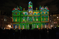 """LYON, FRANCE - DECEMBER 07:Festival of Lights on December 7, 2013 in Lyon. <br /> City Hall.<br /> Spectacular light works by 120 designers will be on show over four days along will attract some three million visitors to the historic city.<br /> In france, each year on December 8, The Festival of Lights expresses gratitude toward Virgin Mary<br /> According to the people, the Festival of Lights celebrates Mary who stopped plague in 1643. The municipal councillors (échevins) had promised to pay tribute to Mary if she saved the town<br /> Since this year, a solemn procession makes its way to the Basilica of Fourvière to candles light and gives offerings in the name of Mary. <br /> This lyonnaise tradition dictates that everyone places candles outsides on all the windows to produce a spectacular effect throughout the streets. Each year, over 4 million tourists come to Lyon for this event.<br /> This festival is probably one of the three biggest festive gatherings in the world in terms of attendance.<br /> And through time, this act of faith in Lyon has been perpetuated by all families and in all religions.<br /> <br /> It is a gesture of joy and gratitude.<br /> Nothing obliges people of Lyon to put these small candles but many of them, away from home, in Paris, Rome, Hong Kong or New York, on December 8, will put in a glass a piece of candle on the edge of their windows, and will think """"I'm from Lyon too.""""<br /> Bruno Vigneron/Getty Images)"""