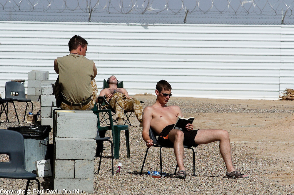Three  British soldiers  serving with the Muliti National Division one in civilian clothes spends time relaxing, reading chatting and sunbathing, while off duty at Basra Air Station during Op Telic Iraq 2005