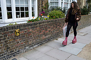 Woman wearing pink leopard skin print platform boots in the upmarket area of Chelsea on 14th April 2021 in London, United Kingdom. Chelsea is one of the principal areas for exclusive, luxury goods in West London. It is known as a district where the rich and wealthy shop, mostly for high end fashion and jewellery.