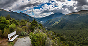 Haast Pass Lookout (walk 4km round trip steeply with 130 meters gain) in the Southern Alps, Mount Aspiring National Park, South Island of New Zealand. Haast Pass  was named from Julius von Haast, a 19th-century explorer who also served as Provincial Geologist for the Provincial government of Canterbury. The road through Haast Pass (State Highway 6) was converted from a rough track to a formed road in 1966 and finally received a complete tarmac surface by 1995. At 562 metres elevation, Haast Pass is the saddle between the valleys of the Haast and Makarora Rivers. The pass forms part of the boundary between Otago and the West Coast. This image was stitched from multiple overlapping photos.