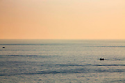 Two fishing trawler boats sailing and fishing in the calm waters of The English Channel at sunset photographed from Folkestone, Kent, England, United Kingdom.